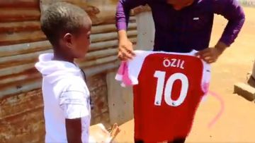 Lawrence Masira, un niño keniano admirador de Mesut Özil, al recibir de él una camiseta del Arsenal