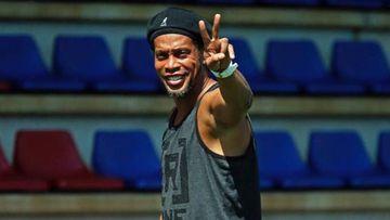 Ronaldinho haciendo la señal de victoria en un campo de fútbol vacio
