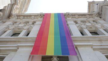 Archivo - Bandera LGTBI colacada en la parte izquierda de la fachada del Palacio de Cibeles, sede del Ayuntamiento de Madrid, durante las fiestas del Orgullo Gay 2019.