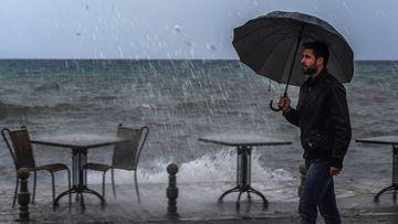 Un hombre camina junto al lago Ohrid durante un día tormentoso en Ohrid, Macedonia, el 30 de noviembre del 2017. EFE/Georgi Licovski