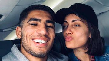 El futbolista Achraf Hakimi con la actriz Hiba Abouk posando sonrientes en un avión.