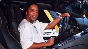 Ronaldinho sonriendo al volante de un coche.